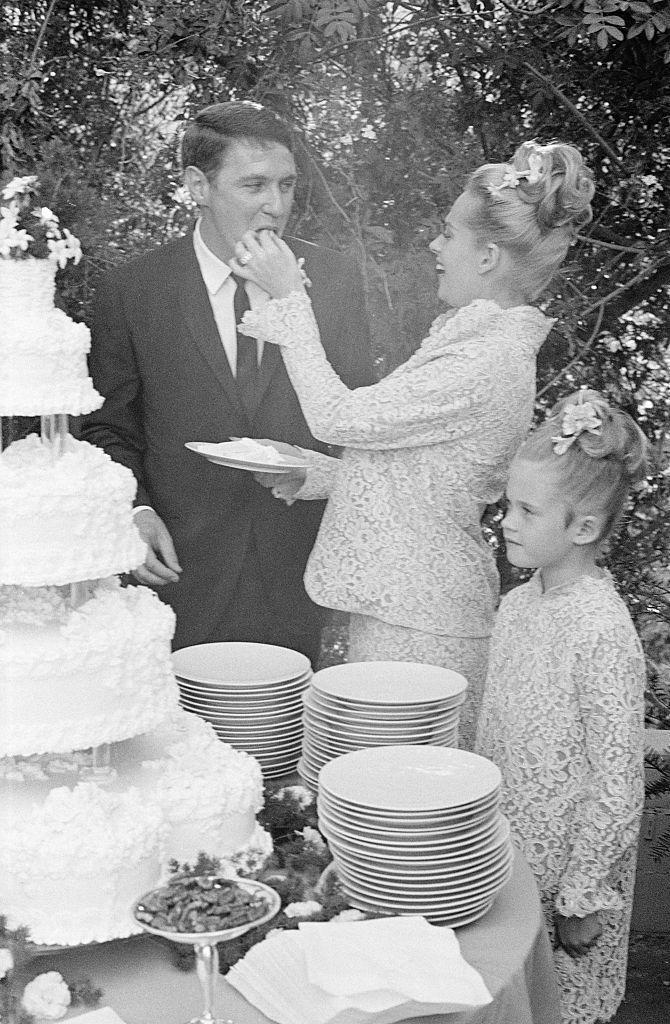<p>Film actress Tippi Hedren shares a piece of cake with her talent agent husband on their wedding day, September 30, 1964. This marked the second walk down the aisle for <em>The Birds </em>star. The two later divorced in 1982, and Hedren went on to marry once more.</p>