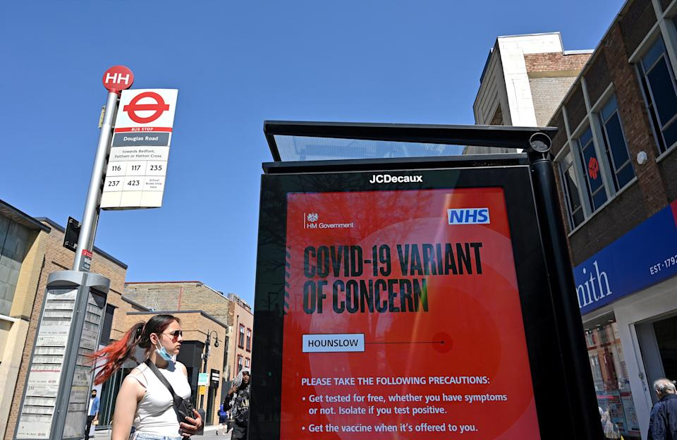 A woman waits at a bus stop byt a sign warning members of the public about a