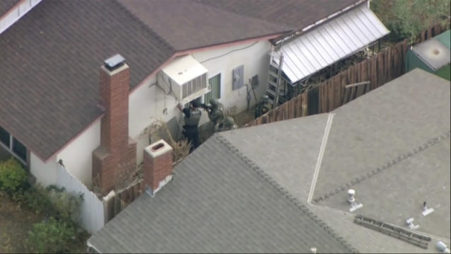 Police search a home in connection with shooting at Saugus High School after reports of a shooting on Thursday, Nov. 14, 2019 in Santa Clarita, Calif. Los Angeles County Sheriff Alex Villanueva tweeted that the suspect was in custody and was being treated at a hospital. He said the suspect was a student but gave no further information. (KTTV-TV via AP)