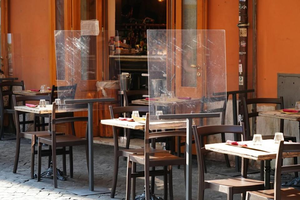 Empty tables outside a restaurant. Plastic, plexiglass screens on for customer separation.