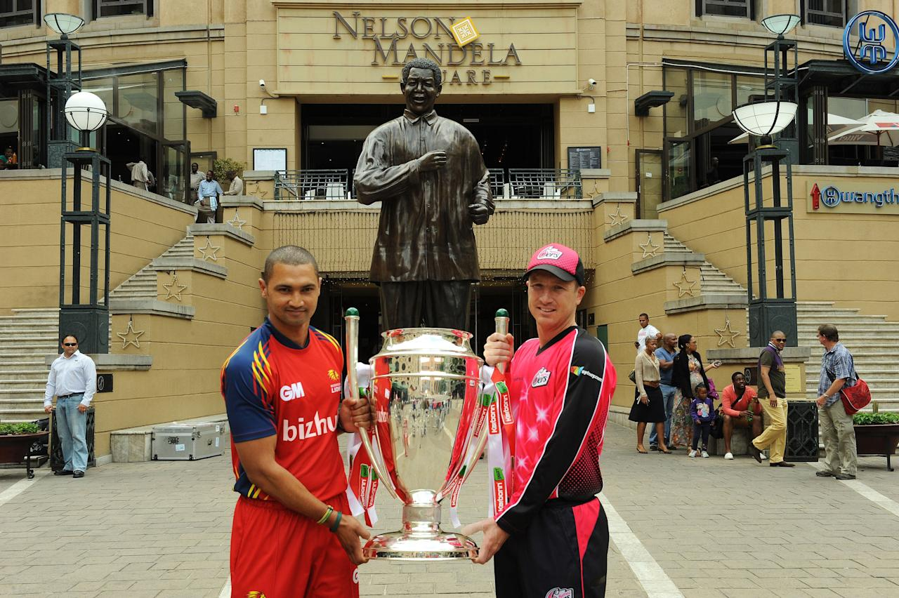 JOHANNESBURG, SOUTH AFRICA - OCTOBER 2:  Captains Alviro Petersen of the Highveld Lions and Brad Haddin (R) of the Sydney Sixers pose with the Trophy during the Karbonn Smart CLT20 Captains photocall session at Sandton Mandela Square on October 28, 2012 in Johannesburg, South Africa.  (Photo by Duif du Toit/Gallo Images/Getty Images)