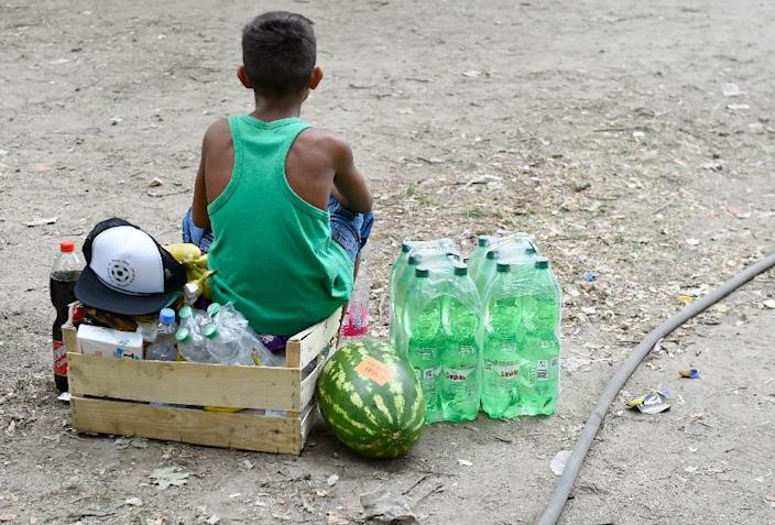 A young boy sits by food brought by citizens outside the State Office of Health and Social Affairs Berlin where refugees wait to receive help from the administration, August 7, 2015 (AFP Photo/Tobias Schwarz)