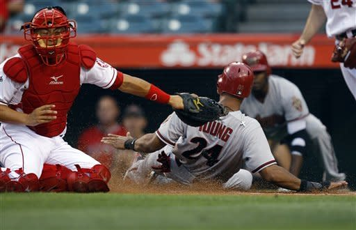 Arizona Diamondbacks' Chris Young (24) scores on a single by teammate Jason Kubel as Los Angeles Angels catcher Hank Conger, left, applies a late tag in the first inning of a baseball game in Anaheim, Calif., Friday, June 15, 2012. (AP Photo/Jae C. Hong)