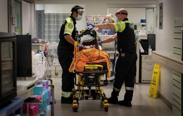 Paramedics transport a patient into the emergency department at Scarborough General Hospital in Toronto earlier this month. (Evan Mitsui/CBC - image credit)