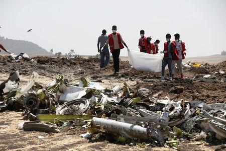 Ethiopian Red Cross workers carry a body bag with the remains of Ethiopian Airlines Flight ET 302 plane crash victims at the scene of a plane crash, near the town of Bishoftu, southeast of Addis Ababa, Ethiopia March 12, 2019. REUTERS/Baz Ratner