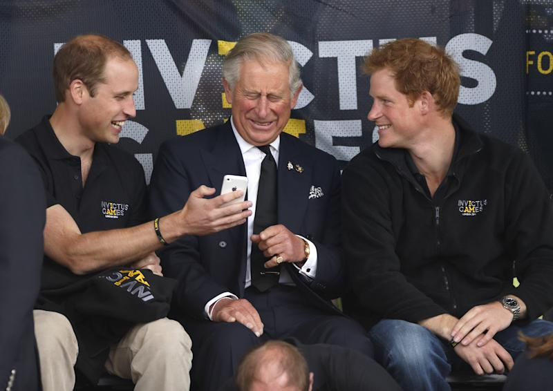 LONDON, UNITED KINGDOM - SEPTEMBER 11: (EMBARGOED FOR PUBLICATION IN UK NEWSPAPERS UNTIL 48 HOURS AFTER CREATE DATE AND TIME) Prince William, Duke of Cambridge, Prince Charles, Prince of Wales & Prince Harry look at a mobile phone as they watch the athletics during the Invictus Games at the Lee Valley Athletics Centre on September 11, 2014 in London, England. (Photo by Max Mumby/Indigo/Getty Images)