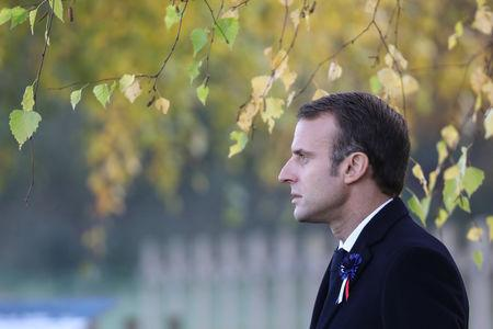 French President Emmanuel Macron arrives to pay his respect by the tomb of Lieutenant Robert Porchon, brother-in-arms of French writer Maurice Genevoix, at the Trottoir necropolis in Les Eparges