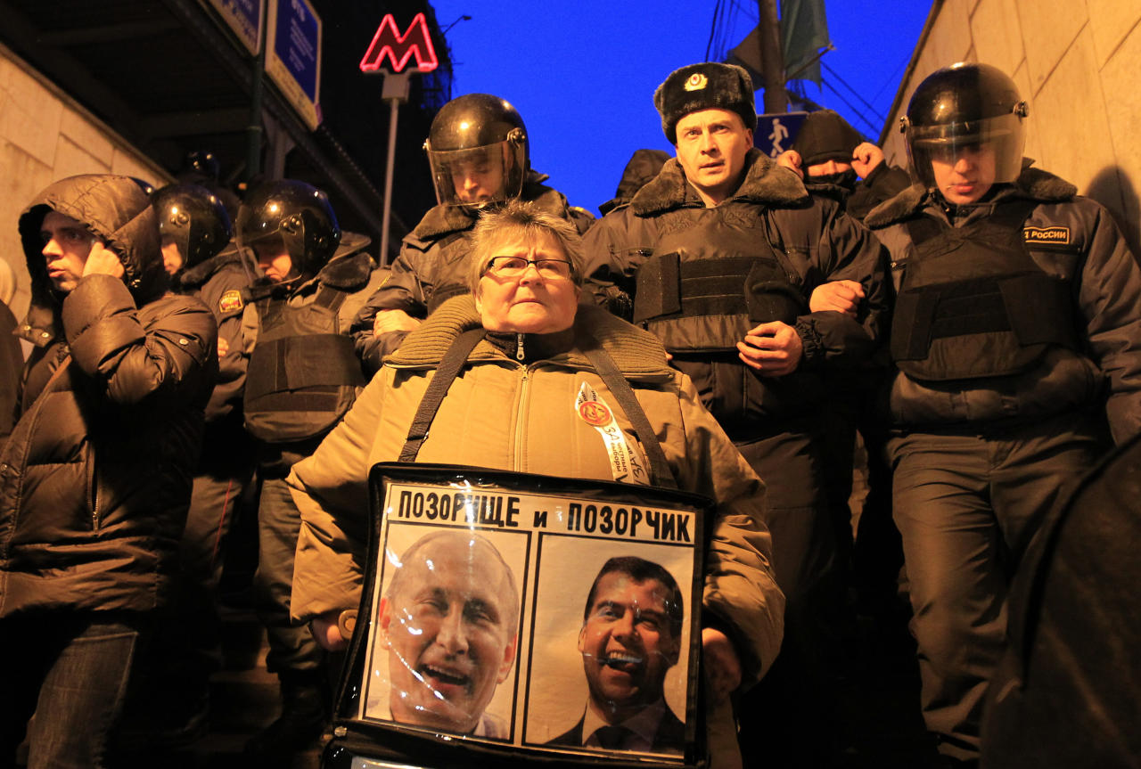 Police officers detain an opposition activist during an unsanctioned protest in Lubyanka Square in Moscow, Monday, March 5, 2012. Police quickly rounded up Eduard Limonov, the leader of the banned National Bolshevik Party and several dozen of his supporters, who attempted to hold an unsanctioned protest near the headquarters of Russia's main security agency. A poster denounces Russian president Dmitry Medvedev and prime minister Vladimir Putin.  (AP Photo/Sergey Ponomarev)