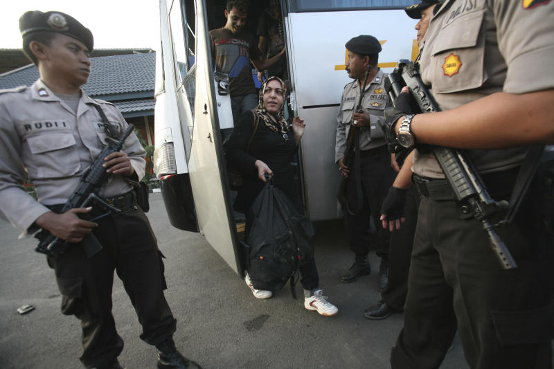 "FILE - In this July 29, 2012 file photo, asylum seekers who were rescued from a troubled boat adrift in heavy seas off Java while trying to reach Australia, are escorted by police officers upon arrival at a local marine police station in Surabaya, East Java, Indonesia. Australia calls it a ""closing-down sale"" for people smugglers: Asylum-seekers in rickety boats have been reaching its shores in record numbers to avoid a tougher new deportation policy the country is preparing to implement. For many migrants, the price of haste may be death. (AP Photo/Trisnadi, File)"