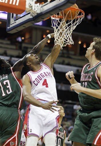 Charlotte Bobcats' Derrick Brown (4) dunks the basketball in between Milwaukee Bucks' Ekpe Udoh (13) and Mike Dunleavy (17) in the first half of an NBA basketball game in Charlotte, N.C., Friday, March 23, 2012. (AP Photo/Bob Leverone)