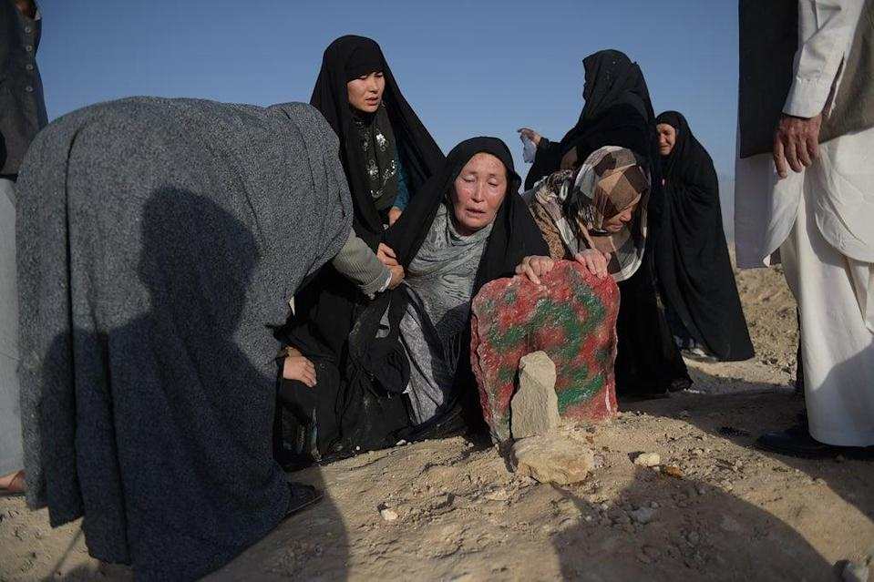 An elderly mother mourns at the grave of her Hazara son after he was killed in the 23 July twin suicide attack in Kabul in 2016 (Getty)