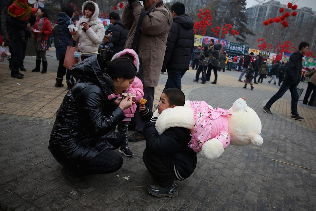 BEIJING, CHINA - FEBRUARY 11: A woman and her son eat bean curd at a Spring Festival Temple Fair for celebrating Chinese Lunar New Year of Snake on February 11, 2013 in Beijing, China. The Chinese Lunar New Year of Snake also known as the Spring Festival, which is based on the Lunisolar Chinese calendar, is celebrated from the first day of the first month of the lunar year and ends with Lantern Festival on the Fifteenth day.  (Photo by Feng Li/Getty Images)