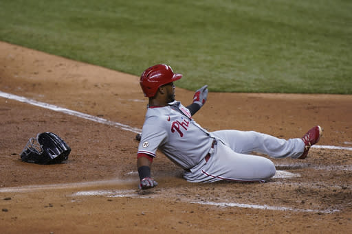 Philadelphia Phillies' Jean Segura slides into home safely on a sacrifice bunt by Adam Haseley during the fourth inning of a baseball game against the Miami Marlins, Thursday, Sept. 10, 2020, in Miami. (AP Photo/Wilfredo Lee)