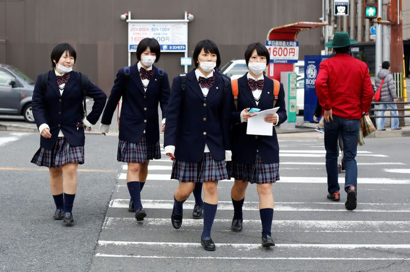 FILE PHOTO: Schoolgirls, wearing surgical masks, cross a street at lunchtime in Kyoto, western Japan