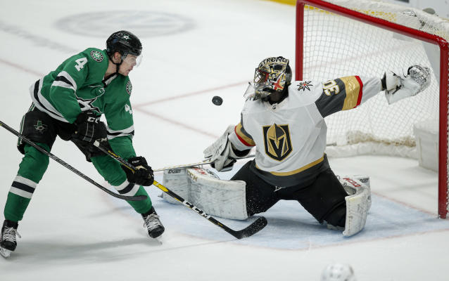 Vegas Golden Knights goaltender Malcolm Subban (30) deflects a shot from Dallas Stars defenseman Miro Heiskanen (4) during overtime of an NHL hockey game Friday, Dec. 13, 2019, in Dallas. The Golden Knights won 3-2 in overtime. (AP Photo/Brandon Wade)
