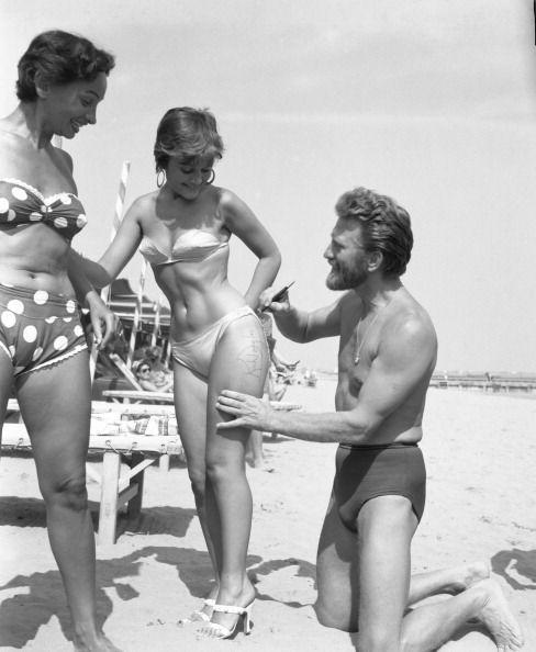 <p>Douglas autographs the thigh of painter Novella Parigini on Lido Beach in Venice. This was at the peak of his heartthrob days.</p>