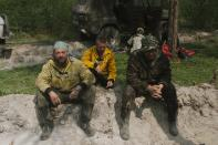 Members of Avialesookhrana crew rest as they dig a moat to stop a forest fire at Gorny Ulus area west of Yakutsk, Russia, Thursday, July 22, 2021. The hardest hit area is the Sakha Republic, also known as Yakutia, in the far northeast of Russia, about 5,000 kilometers (3,200 miles) from Moscow. About 85% of all of Russia's fires are in the republic, and heavy smoke forced a temporary closure of the airport in the regional capital of Yakutsk, a city of about 280,000 people. (AP Photo/Ivan Nikiforov)