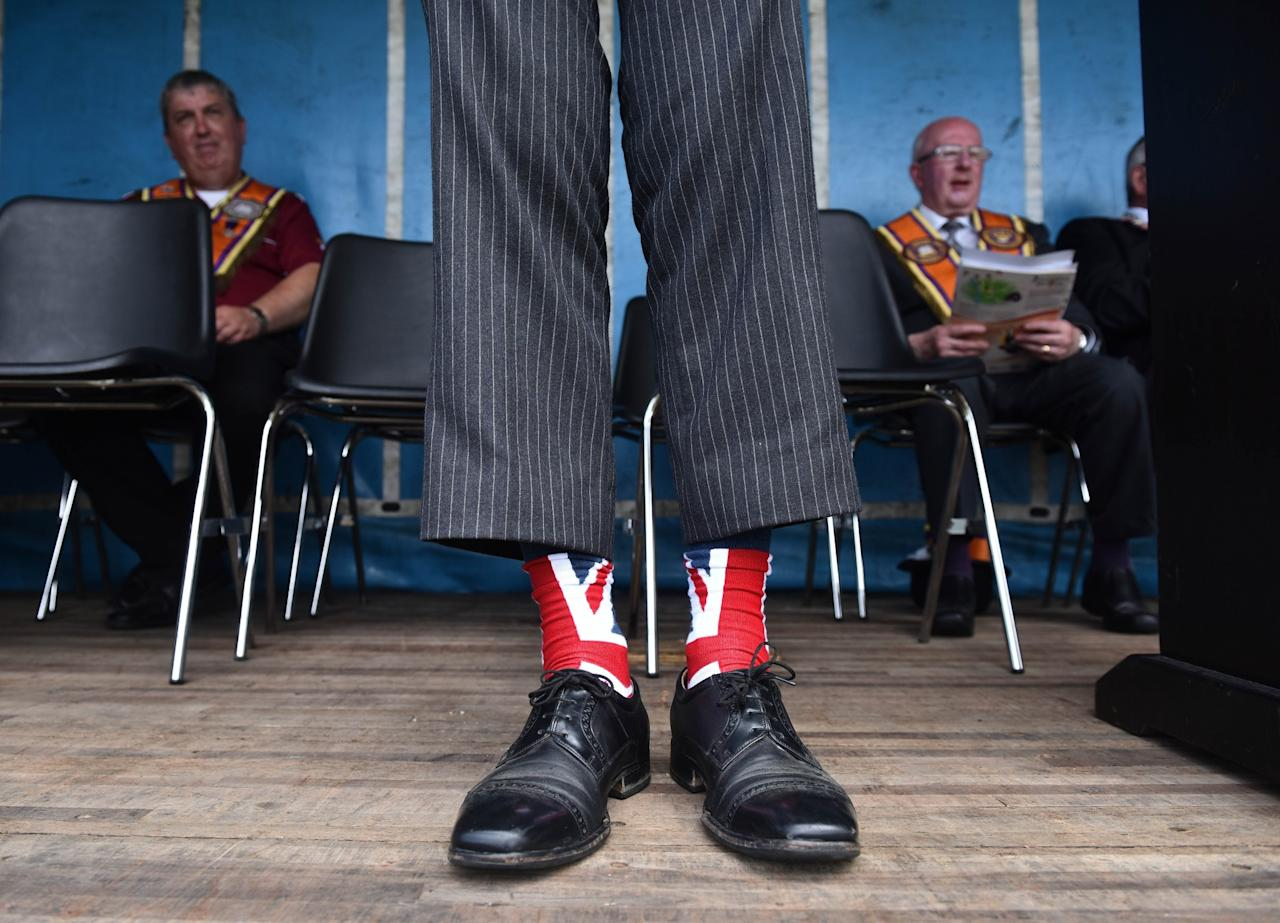 <p>One of the platform party displays his Union Jack socks as the Independent Orange Lodge holds its annual parade in Rasharkin, Northern Ireland (Getty Images) </p>
