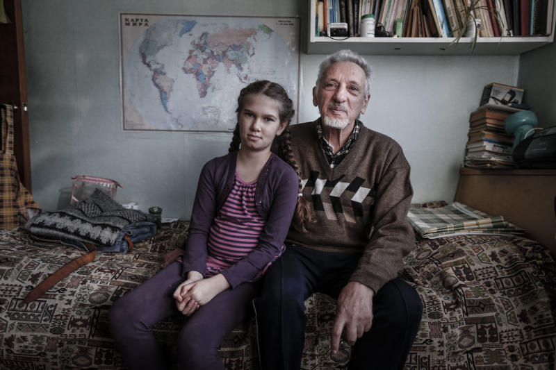 In this Sunday Nov. 11, 2012 photo from left: Maya Rozina, 8, and Anatoly Rozin, 78, pose at their apartment in Moscow. The four generations of Zimanenko- Rozin's family embody the history of Jews in Russia over the past century, from the restrictions of czarist times to the revival of Jewish culture in Russia today. (AP Photo/Sergey Ponomarev)