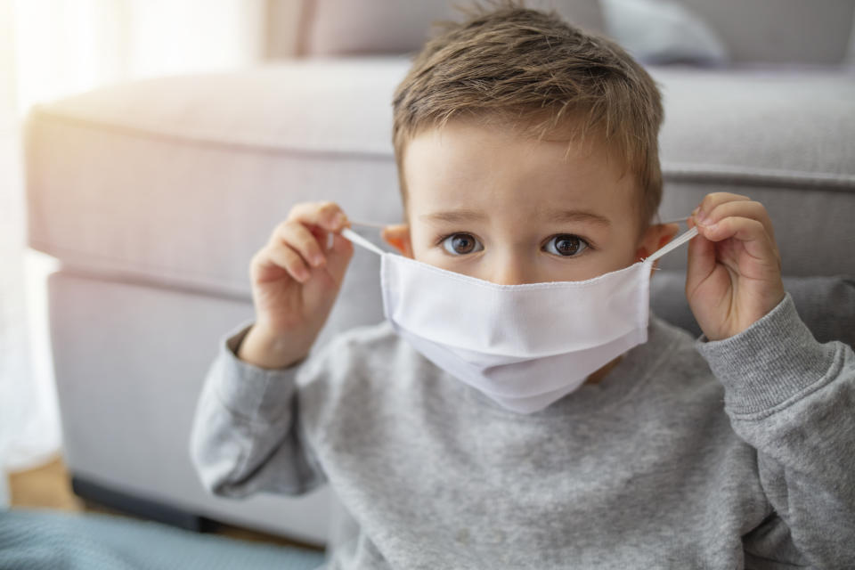 Young child wearing a respiratory mask as a prevention against the Coronavirus Covid-19. Little boy wearing anti virus mask staying at home. Protection against flu and virus infection
