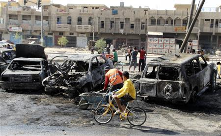 A youth cycles past a man clearing up at the site of a car bomb in Baghdad's al-Shaab district, October 27, 2013. REUTERS/Thaier Al-Sudani
