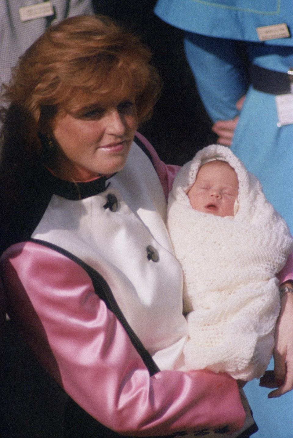 <p>Sarah, Duchess of York leaves the Portland Hospital in London with her new daughter, Princess Eugenie, in March 1990. (Colin Davey/Getty Images)</p>