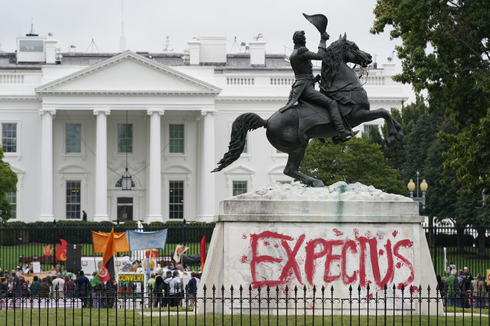 """The words """"Expect Us"""" are painted on the base of the equestrian statue of President Andrew Jackson in Lafayette Park as protesters gather to call on the Biden administration to do more to combat climate change and ban fossil fuels outside the White House in Washington, Tuesday, Oct. 12, 2021. The words are part of the phrase """"Respect Us, or Expect Us"""" which indigenous women have been using while protesting oil company Enbridge's Line 3 pipeline through Minnesota. (AP Photo/Patrick Semansky)"""