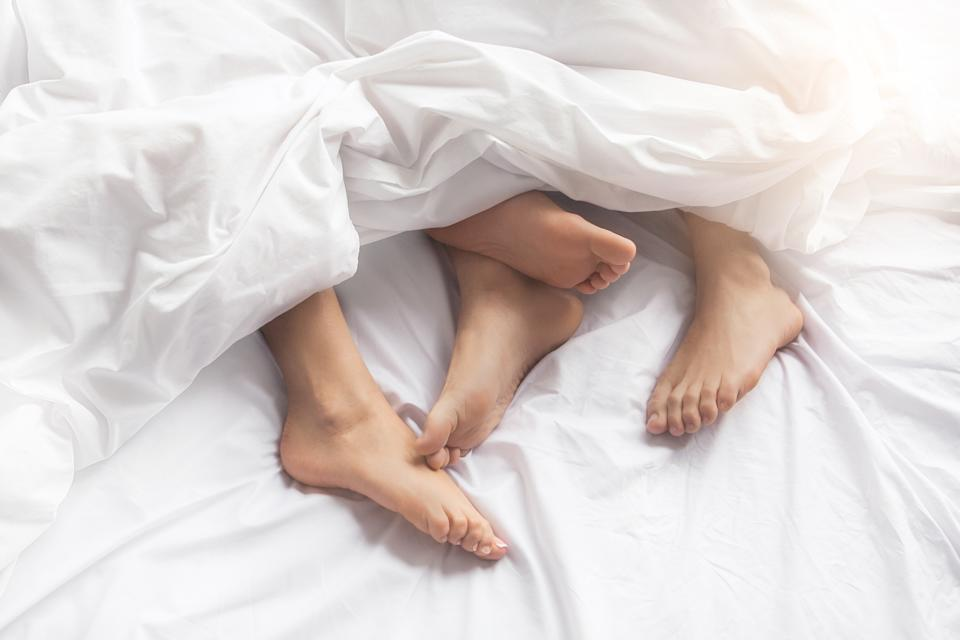 Young couple man and woman intimate relationship on bed feet