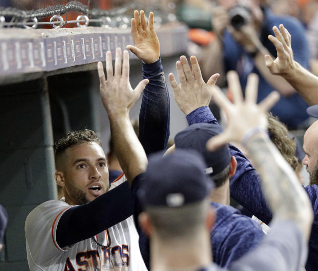 Houston Astros' George Springer, left, is congratulated in the dugout after scoring a run against the San Francisco Giants during the third inning of a baseball game Tuesday, May 22, 2018, in Houston. (AP Photo/David J. Phillip)