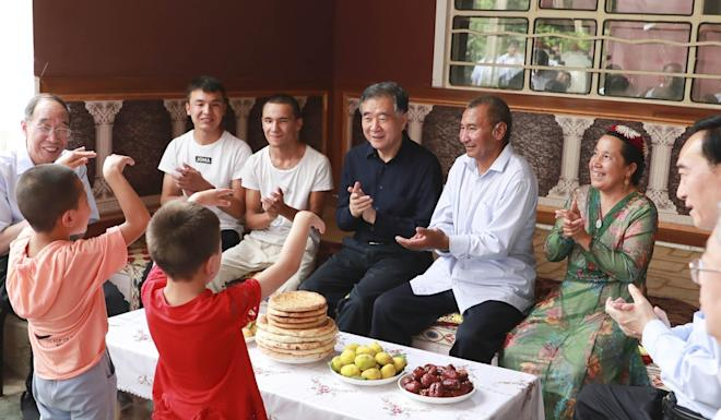 Wang Yang (seated, centre) during a visit to the village of Hotan in China's Xinjiang region on Monday. Photo: Xinhua