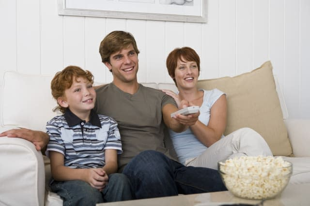 Family watching television on couch