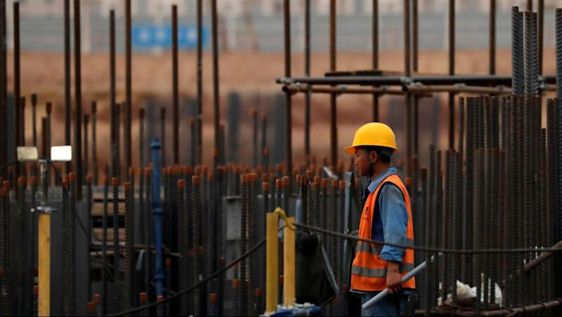 A Chinese construction labourer works at the site of the future Iconic Tower skyscraper being built east of Cairo.