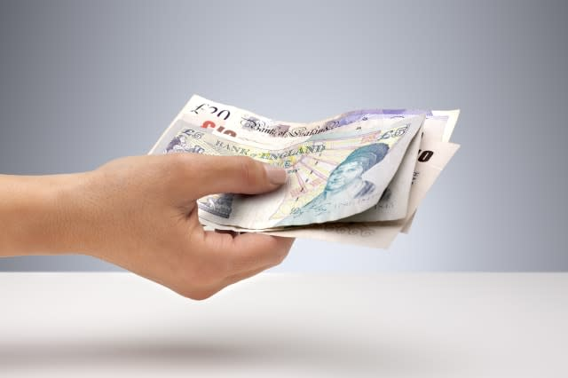 Hand holding out a selection of UK pounds sterling currency