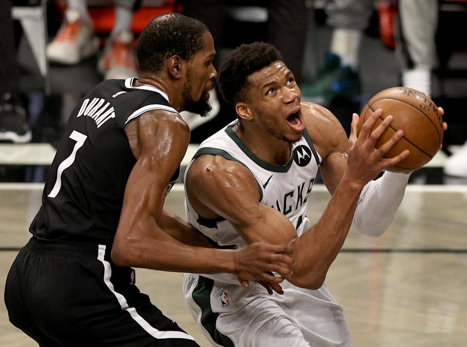 NEW YORK, NEW YORK - JUNE 19: Giannis Antetokounmpo #34 of the Milwaukee Bucks heads for the net as Kevin Durant #7 of the Brooklyn Nets defends in the second half during game seven of the Eastern Conference second round at Barclays Center on June 19, 2021 in the Brooklyn borough of  New York City. NOTE TO USER: User expressly acknowledges and agrees that, by downloading and or using this photograph, User is consenting to the terms and conditions of the Getty Images License Agreement. (Photo by Elsa/Getty Images)