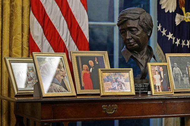 PHOTO: Photos of President Joe Biden's family and a A bust of Latino American civil rights activist Cesar Chavez are displayed behind the Resolute desk in the Oval Office just hours after his inauguration on Jan. 20, 2021 in Washington, D.C. (Chip Somodevilla/Getty Images)