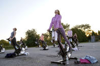 Donna Coskren, of Newburyport, Mass., front, stretches with others while on stationary exercise bikes during a spinning class in a parking lot outside Fuel Training Studio, Monday, Sept. 21, 2020, in Newburyport. The gym's revenue is down about 60% during the COVID-19 pandemic. Fuel Training Studio plans to continue holding outdoor classes into the winter with the help of a planned greenhouse-like structure with heaters but no walls. (AP Photo/Steven Senne)