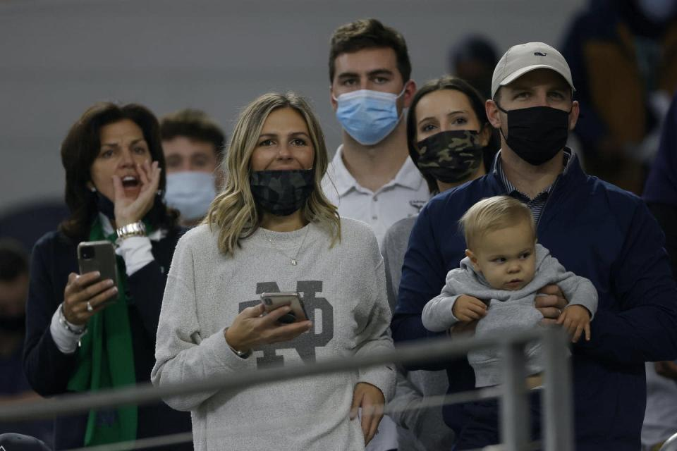 People standing close together, most wearing masks.