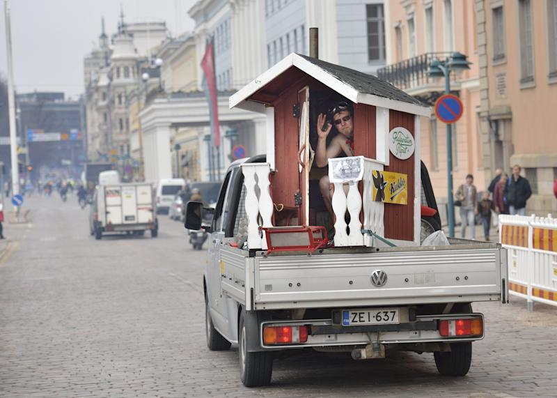 In this May 10, 2013 photo, a man waves from a mobile sauna by the Market Square in Helsinki, Finland. . Invented by the Finns, saunas are source of national pride and most private homes have them. (AP Photo/Pekka Sakki, Lehtikuva) FINLAND OUT