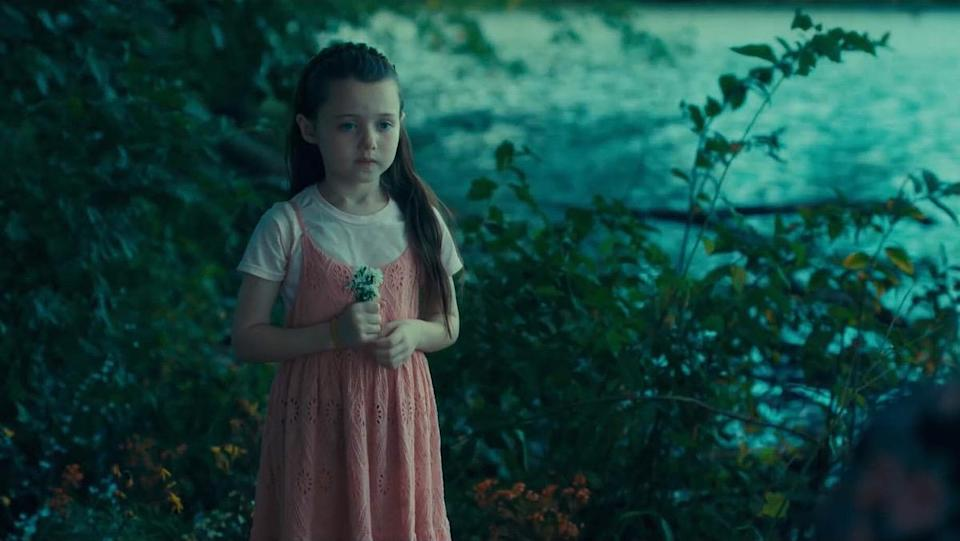 A young girl played by Violet McGraw holds flowers and stands near a body of water in a scene from Doctor Sleep.