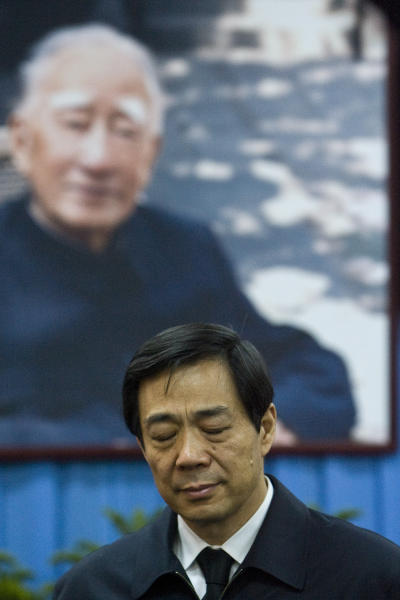 FILE - In this Jan. 17, 2007 file photo, Bo Xilai, then China's Minister of Commerce, attends a memorial ceremony for his father Bo Yibo, a late communist leader considered one of communist China's founding fathers, in front of the father's photo at a military hospital in Beijing. Disgraced Chinese politician Bo was expelled from the ruling Communist Party on Friday, Sept. 28, 2012, and will face corruption and other criminal charges, the latest step in a scandal that has overshadowed a political transition now set to take place in early November. (AP Photo/Alexander F. Yuan)
