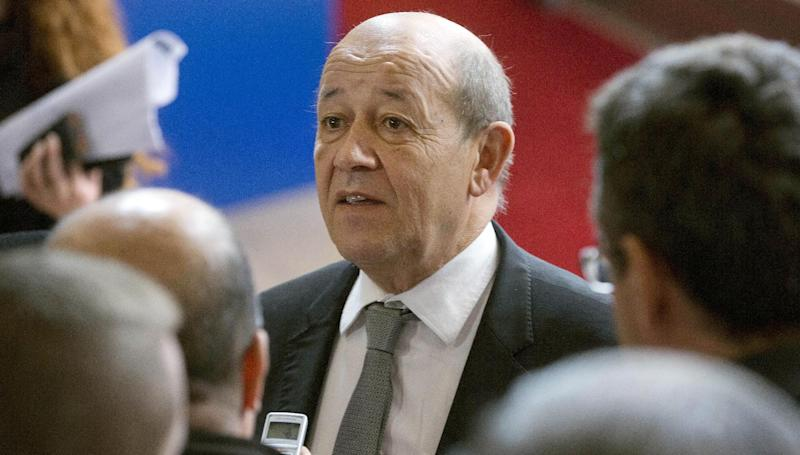 French Defense Minister Jean-Yves Le Drian, center, speaks with journalists as he arrives for a meeting of EU foreign and defense ministers at the EU Council building in Brussels on Tuesday, Nov. 19, 2013. EU foreign and defense ministers meet in Brussels Tuesday to discuss, among other issues, the situation in Libya. (AP Photo/Virginia Mayo)