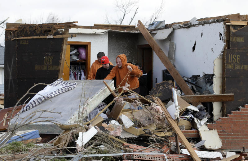 Residents clean up their damaged house in Marysville, Ind., Saturday, March 3, 2012. Massive thunderstorms, predicted by forecasters for days, threw off dozens of tornadoes as they raced Friday from the Gulf Coast to the Great Lakes. Twisters crushed blocks of homes, knocked out cellphones and landlines, ripped power lines from broken poles and tossed cars, school buses and tractor-trailers onto roads made impassable by debris. (AP Photo/Nam Y. Huh)