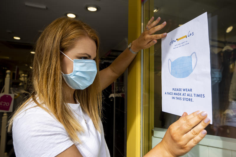 Joanne Millar store manger of Joules in Belfast places a sign in the shop window advising customers that face masks must be worn at all times as face coverings are now compulsory for shoppers in Northern Ireland.