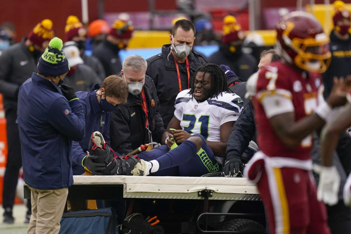 Seattle Seahawks running back DeeJay Dallas (31) reacting to members of the medical team moving him onto a transport cart during the first half of an NFL football game against the Washington Football Team, Sunday, Dec. 20, 2020, in Landover, Md. (AP Photo/Andrew Harnik)