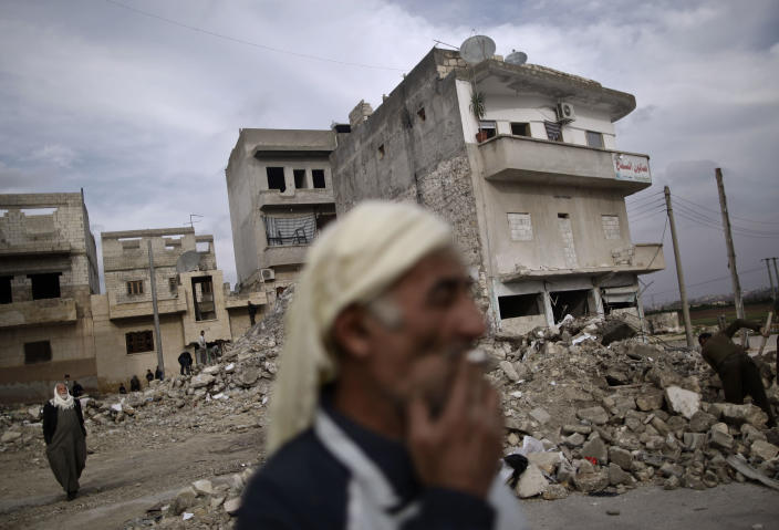 In this Wednesday, Dec. 12, 2012 photo, an elderly Syrian man smokes a cigarette while standing next to a residential building destroyed in a government airstrike, in Maaret Misreen, near Idlib, Syria. The town is broke, relying on a slowing trickle of local donations. The rebels, a motley crew of laborers, mechanics and shopowners, have little experience in government. President Bashar Assad's troops still control the city of Idlib a few miles away, making area roads unsafe and keeping Maaret Misreen cut off from most of Syria. (AP Photo/Muhammed Muheisen)