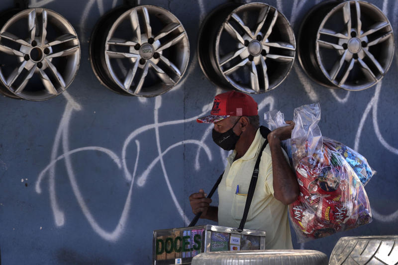 A candy seller wears a mask amid the COVID-19 pandemic in Ceilandia, one of the neighborhoods most affected by the new coronavirus in Brasilia, Brazil, Tuesday, July 21, 2020. (AP Photo/Eraldo Peres)