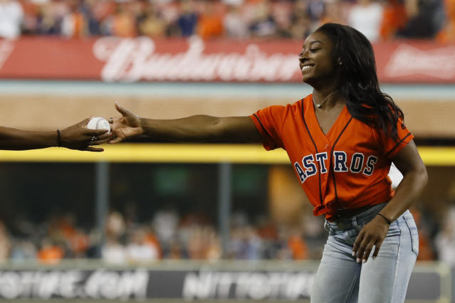 Gymnast Simone Biles is handed the ceremonial first pitch ball before Game 2 of the baseball World Series between the Houston Astros and the Washington Nationals Wednesday, Oct. 23, 2019, in Houston. (AP Photo/Matt Slocum)