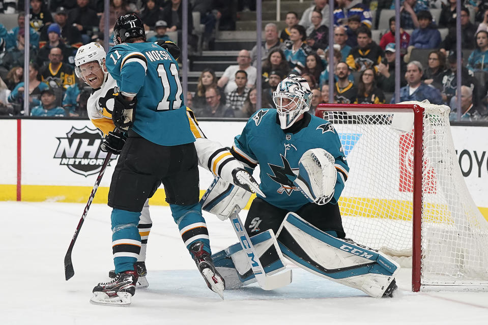 Pittsburgh Penguins right wing Patric Hornqvist (72) collides with San Jose Sharks right wing Stefan Noesen (11) in front of goaltender Martin Jones (31) during the first period of an NHL hockey game Saturday, Feb. 29, 2020, in San Jose, Calif. (AP Photo/Tony Avelar)