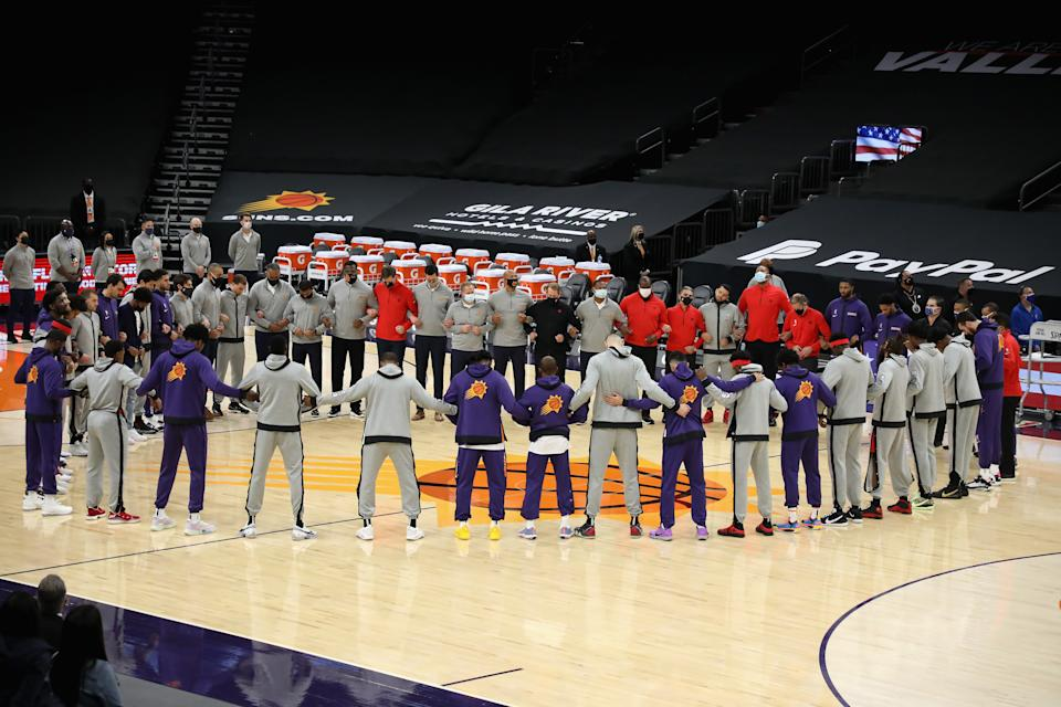 PHOENIX, ARIZONA - JANUARY 06: The Toronto Raptors and the Phoenix Suns stand arm-in-arm during the national anthem before the NBA game at Phoenix Suns Arena on January 06, 2021 in Phoenix, Arizona. NOTE TO USER: User expressly acknowledges and agrees that, by downloading and or using this photograph, User is consenting to the terms and conditions of the Getty Images License Agreement. (Photo by Christian Petersen/Getty Images)