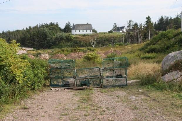 A stack of lobster traps can be seen at a roadside stop that overlooks the Anglican church in Neils Harbour.  (Erin Pottie/CBC - image credit)